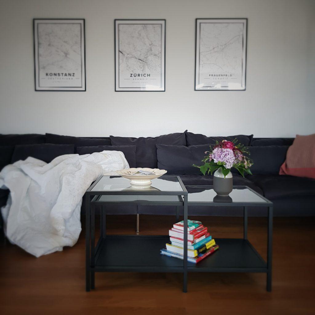 Sofa, Beistelltisch, Landkarten an der Wand