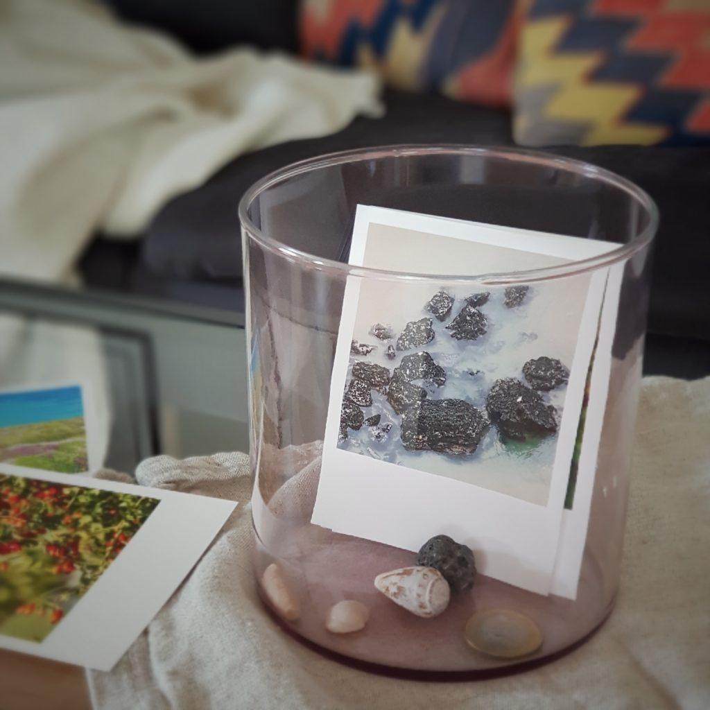Nahaufnahme eines Glases mit Fotos und Muscheln darin