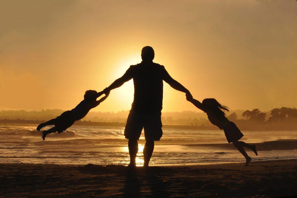 Mann mit Kindern im Sonnenuntergang am Strand