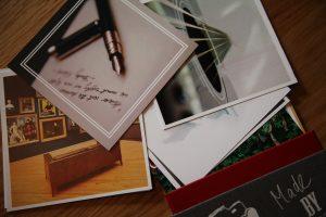 Quadratische Postkarten liegen kreuz und quer übereinander