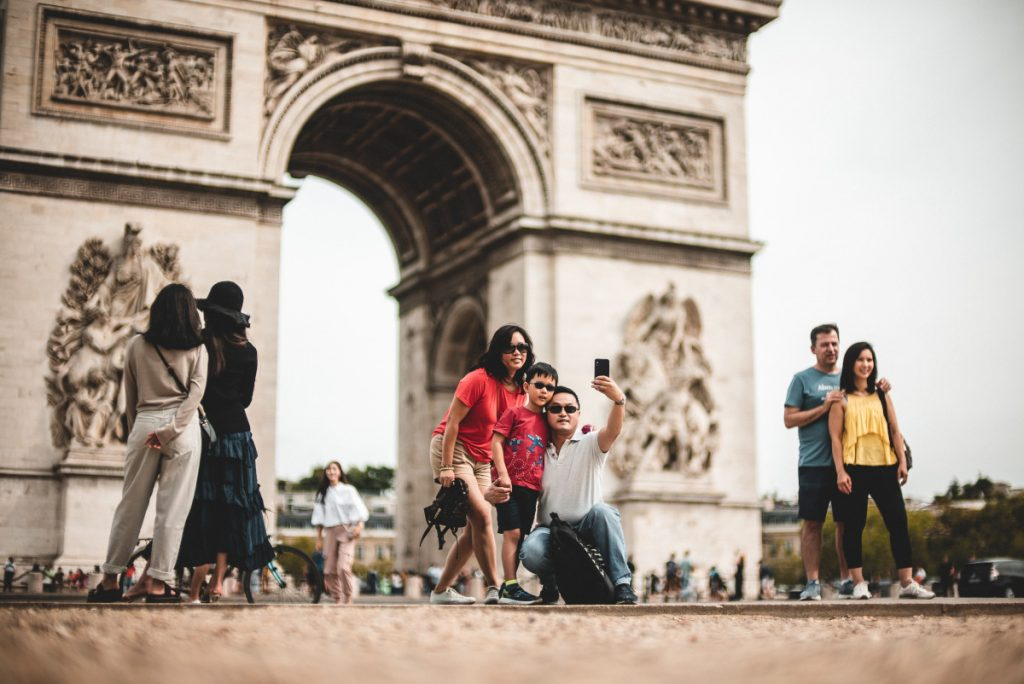 Touristen machen Selfies vor dem Arc de Triomphe