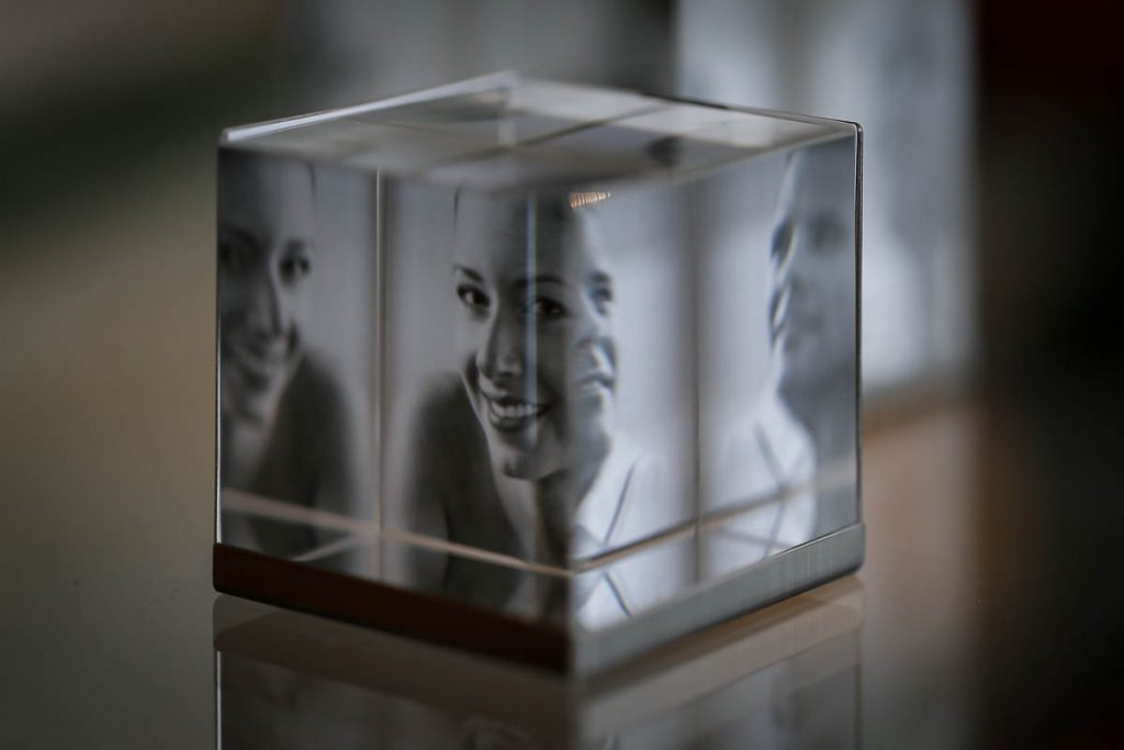 ein Glas-Fotowürfel mit Bildern einer lächelnden Frau im Inneren