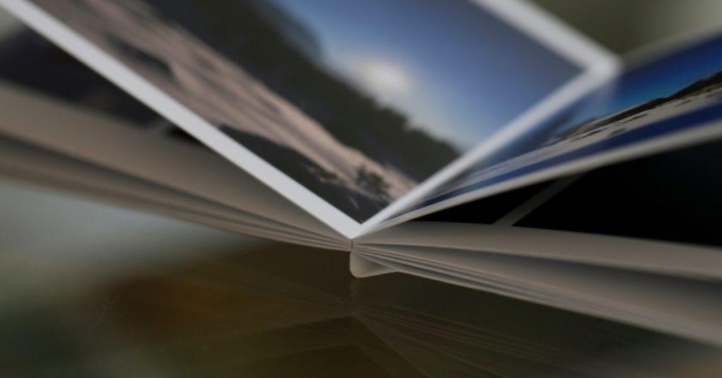 ein aufgeklapptes Fotobuch liegt auf einem Glastisch