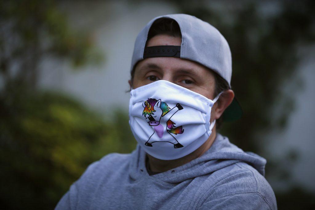 Mann trägt eine Maske mit Einhorn-Motiv